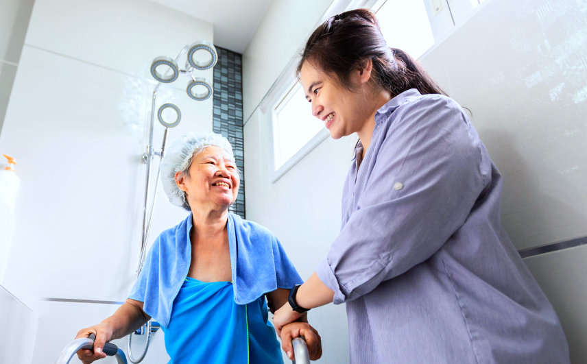 female nurse assisting senior woman bathing