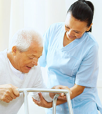 female nurse assisting a senior man to stand up using his walking frame
