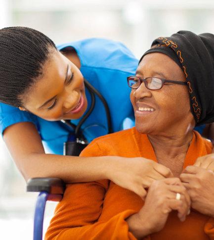 female nurse and senior woman wearing eye glasses smiling