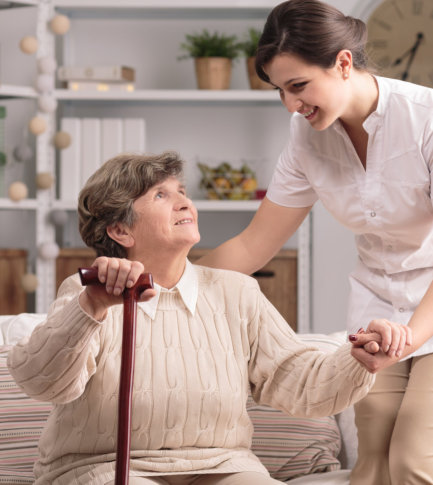 female nurse assisting senior woman to stand up using her walking stick