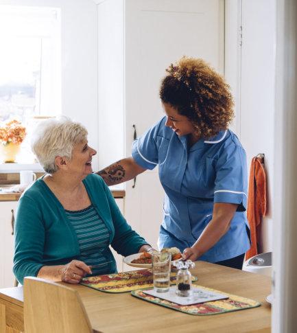 female nurse preparing meals to senior woman smiling
