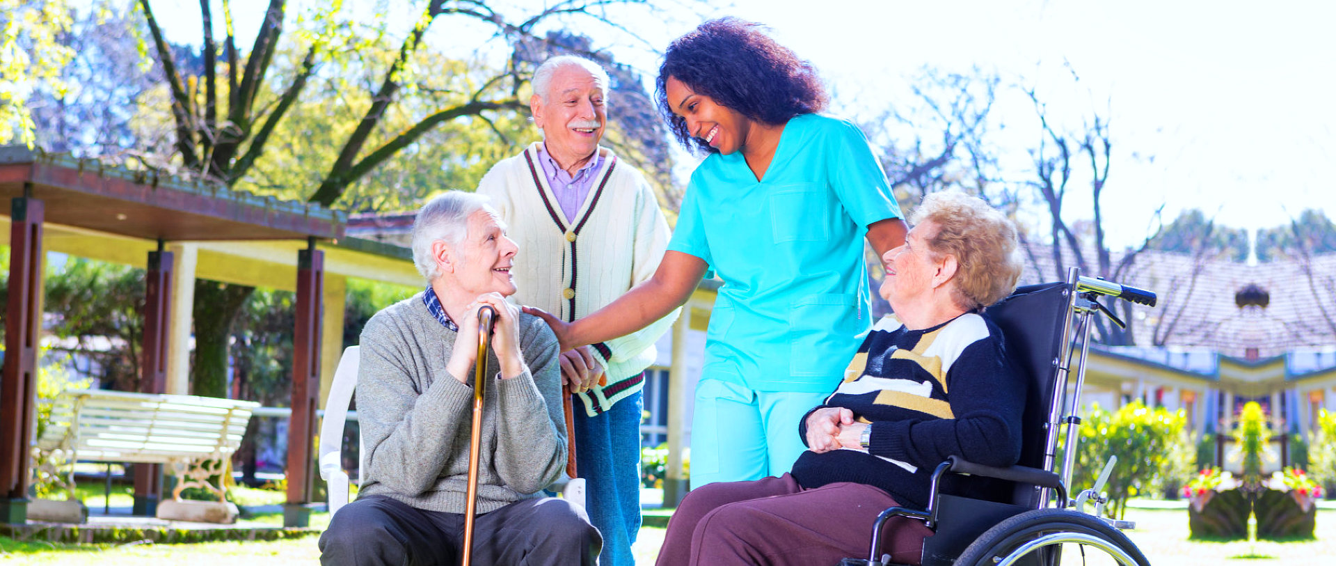 a group of seniors with their nurse smiling outside of the house