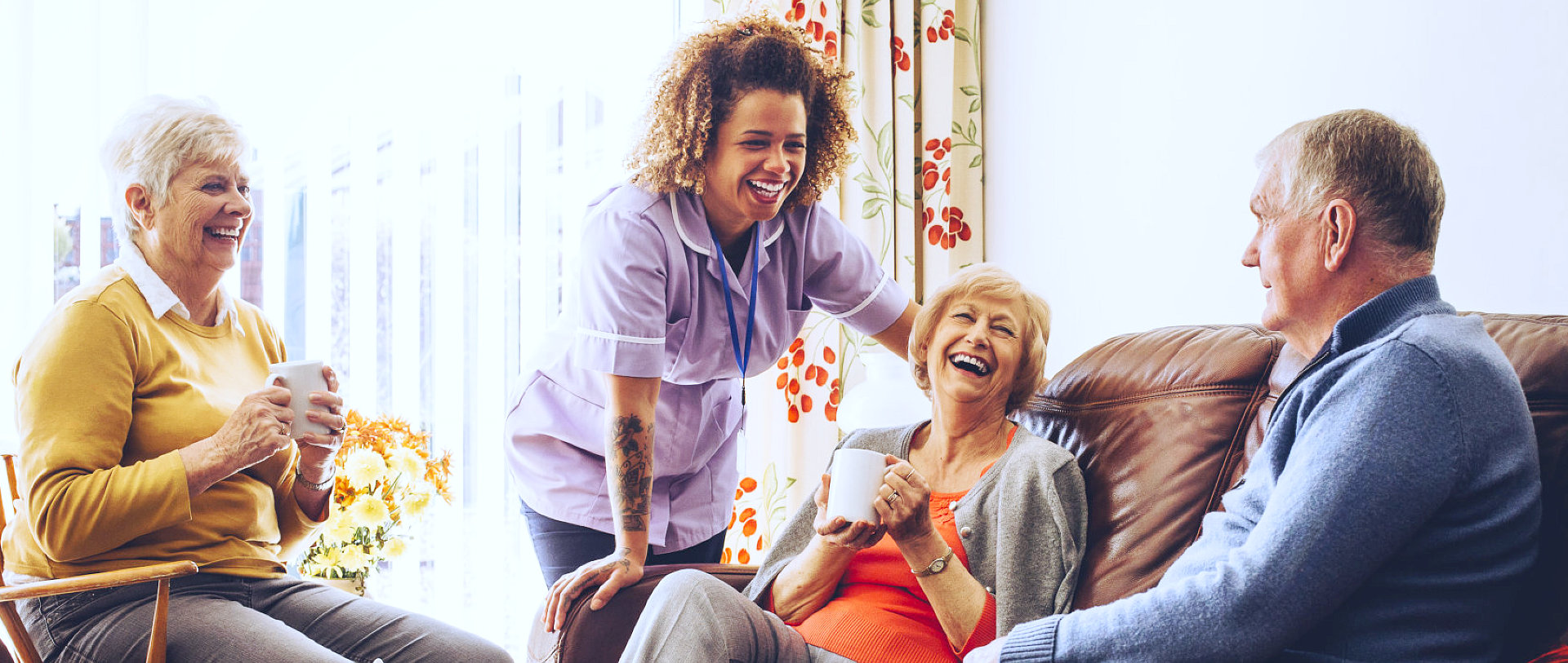 a group of seniors with their nurse smiling in the sofa